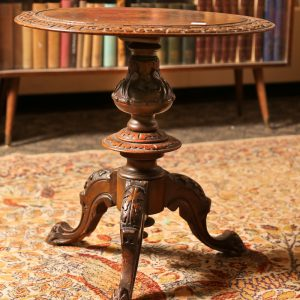 41.  Lamp table. English solid walnut with center inlay depicting a warrior on horseback. With intricate carving overall. Splayed base. Late 19th century.