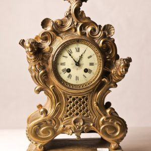 9.  French mantle clock. Roman numeral face and brass case with cherub motif. Late 19th century.