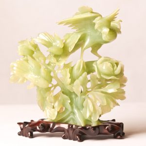 "8.  Chinese serpentine jade carving. Near Celadon colouring, depicting birds on a bush. 7""H. Mid 20th century. On wooden base."