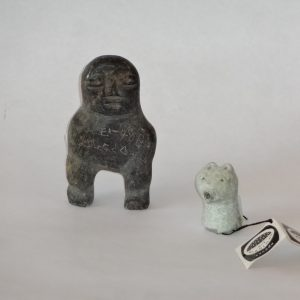 145.  Two Inuit soapstone carvings.  Grey grained figure of a man, signed in syllabics, and jade-coloured Bear's Head, numbered on bottom.