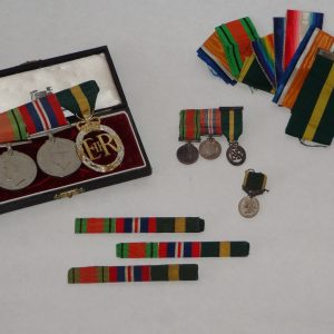 14.  Collection of military medals and stripes. Three WWII British War Medals and their miniatures, ribbon bars and extra ribbon, an additional WWII miniature medal,