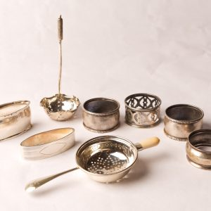 87. Sterling silver collection. Six napkin rings and two strainers. Eight pieces.