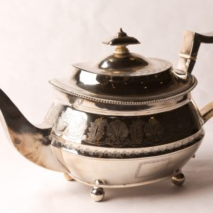 13. Sterling silver teapot. Hand chased foliage design, with ivory stoppers, hinged lid and bun feet. Not monogrammed. Robert and Samuel Hennell, London, 1812.