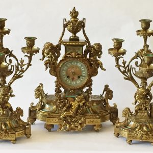35a. Garniture set.  Ornate brass construction with clock and candleabras in cherub and foliate motif.  Mid 20th century.