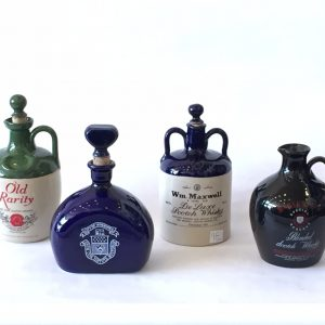 98. Whiskey jug collection. McGibbon's; Bulloch Lade; Wm. Maxwell; and City of Winnipeg collector's bottle.  All with original cork stoppers. Mid 20th century.